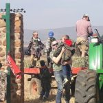 A tractor carrying a young paintball group to the field.